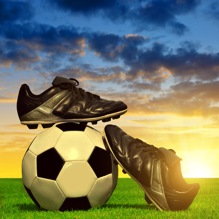Soccer ball and shoes in grass at sunset
