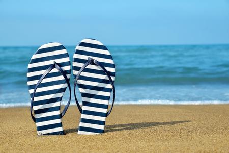 flipflops: Flipflops on a sandy ocean beach. Summer vacation concept.