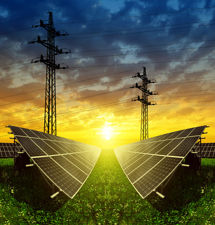 Solar panels with electricity pylons at sunset. Concept of sustainable resources.
