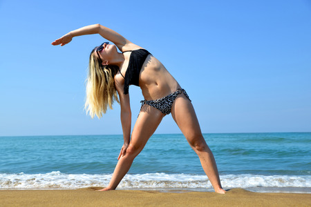 Young woman stretching body on sandy beach Stock Photo