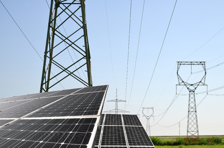 sustainable resources: Solar panels with electricity pylons. Concept of sustainable resources. Stock Photo