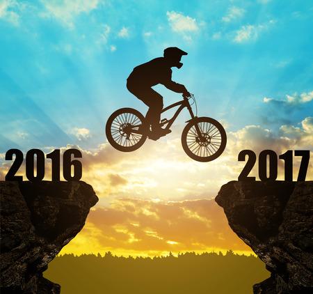 silueta ciclista: Ciclista de la silueta que salta en el Año Nuevo de 2017 a la puesta del sol. Foto de archivo