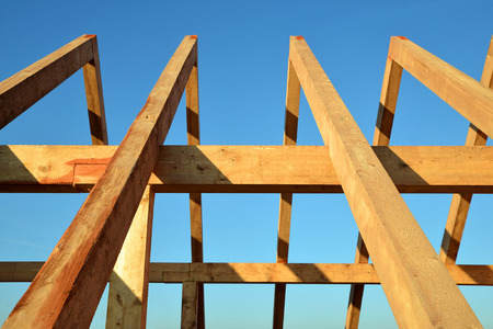 rafters: Wooden Roof frame rafters against a blue sky. Stock Photo