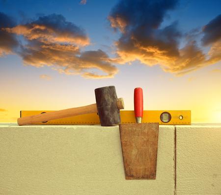 Masonry tools on brick wall at sunset.