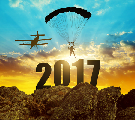 skydiver: Silhouette skydiver parachutist landing in to the New Year 2017 at sunset