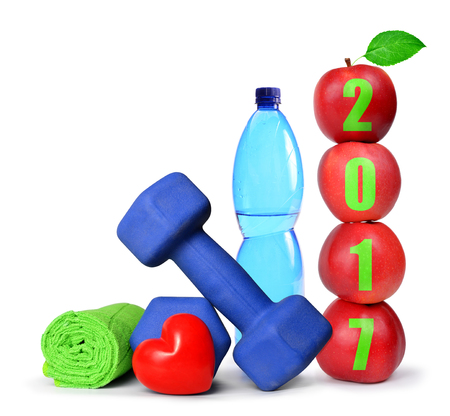 Red apples, dumbbells and PET bottle with drinking water isolated on white. Healthy resolutions for the New Year 2017 Stock Photo
