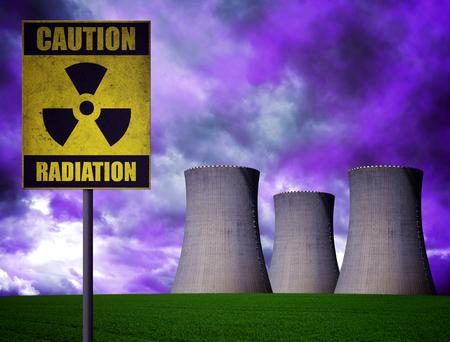 riesgo quimico: Central nuclear con el símbolo de advertencia de radiactividad en el cielo nublado dramático. Foto de archivo