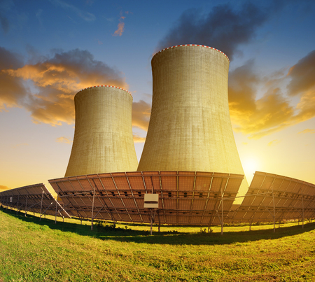 Solar energy panels and nuclear power plant at sunset. Stock Photo