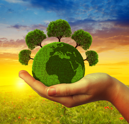 small world: Hand holding green planet with trees at sunset. Concept of environmental protection.