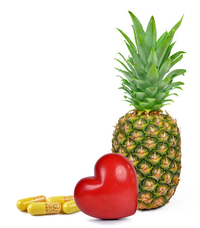 Yellow capsule pills with heart and pineapple isolated on white background.