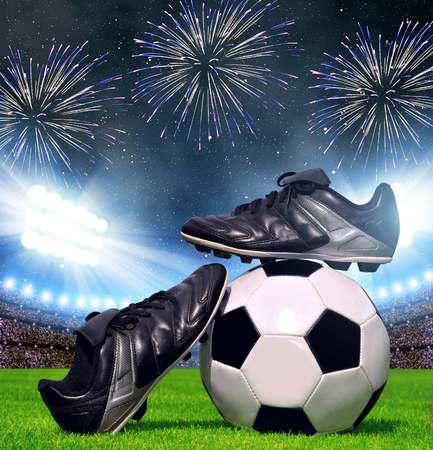 Soccer ball and shoes in grass, football stadium with the dright lights. Stock Photo