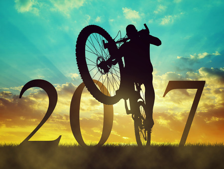 Cyclist with bicycle at sunset. Forward to the New Year 2017 photo