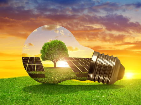 sustainable resources: Solar energy panels in light bulb at sunset. The concept of sustainable resources.