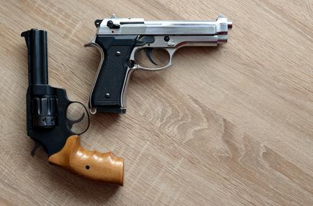 pistols: Two pistols on wooden board. Stock Photo