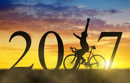 silueta ciclista: Ciclista con la bicicleta en la puesta del sol. Adelante con el Año Nuevo 2017