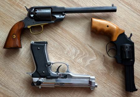 pistols: Three pistols on wooden board. Stock Photo