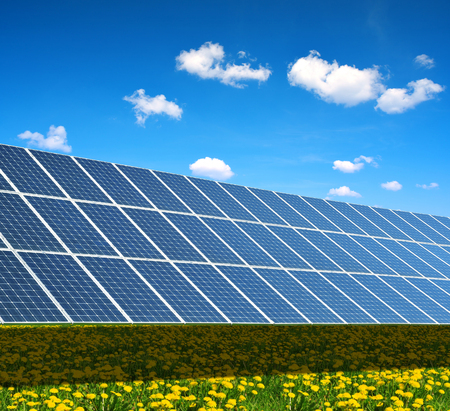 Solar power station on the spring flowering meadow. Photovoltaic panels generate clean energy.