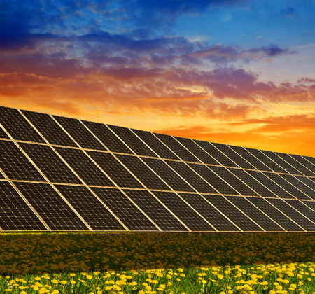 Solar power station on the spring flowering meadow at sunset. Photovoltaic panels generate clean energy.