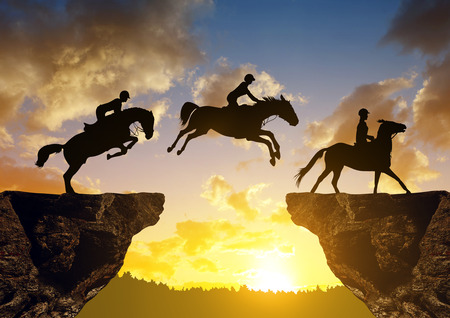 difficult lives: Silhouette of a rider on a horse jumping through the gap between rock at sunset.
