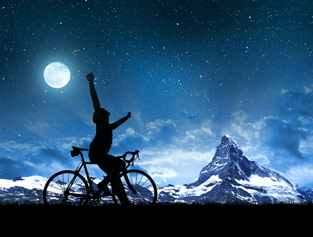 Silhouette cyclists with road bike in the night sky. photo