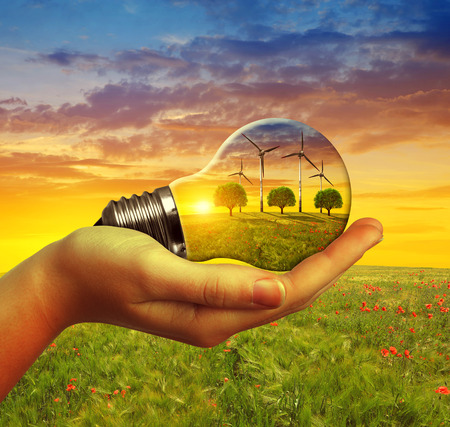 renewable energy: Hand holding eco light bulb with wind turbines at sunset. The concept of sustainable resources. Stock Photo