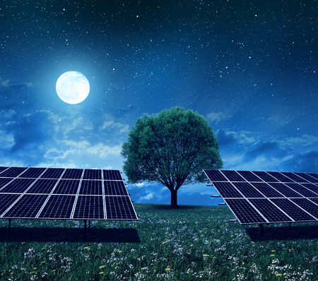 Solar power station on the meadow in night. Photovoltaic panels generate clean energy.