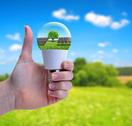 Hand met duim omhoog houdend een eco LEIDENE bol met zonnepaneel. Het concept van duurzame hulpbronnen. Stockfoto