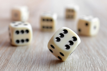 Rolling dice on a wooden desk. Stock Photo