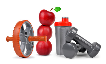 Fitness equipment for exercising abdominal muscles, dumbbells, apples and protein shaker isolated on white background. Concept of healthy lifestyle. Stock Photo