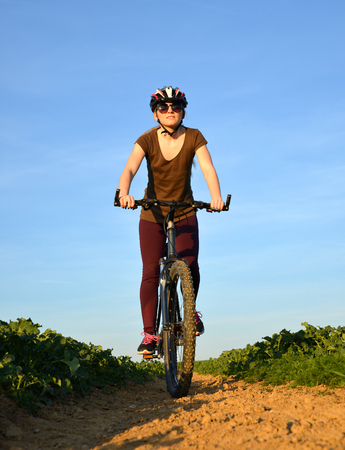 Girl riding a bike on a dirt road.