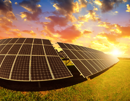 Photovoltaic panels at sunset. Power plant using renewable solar energy. Imagens