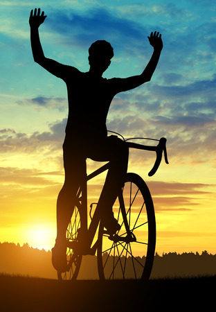 Silhouette of a cyclist on a road bike with his hands above his head in the sunset. photo