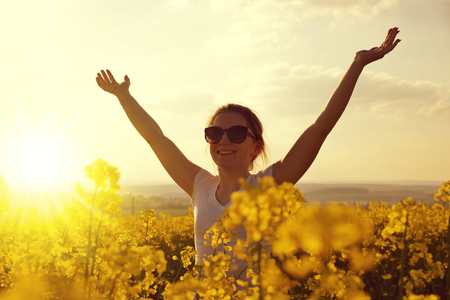 Young happy woman in the rapeseed field at sunset. Stock Photo