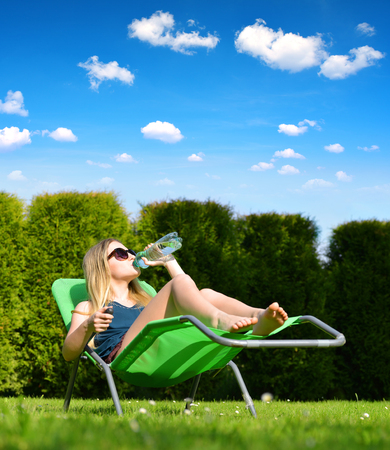 Woman relaxing on lounger in the garden. Stock Photo