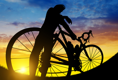 Silhouette of a cyclist on a road bike at sunset. photo