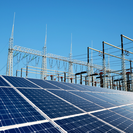Solar energy panels in the background high voltage power substation. Stock Photo