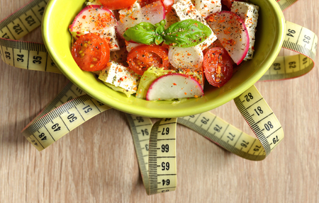 Fresh salad with tofu in bowl and measuring tape on wooden background. Stock Photo