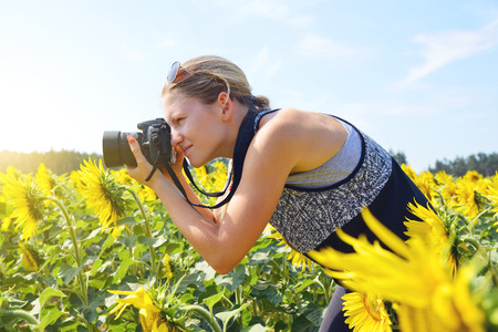 Woman taking photos of sunflower field with digital camera. photo