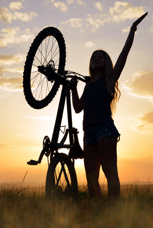 Girl with bicycle in the sunset. photo