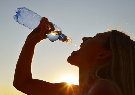 Silhouette of a woman drinking water from bottle at sunset. photo