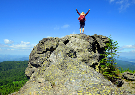 Girl on rock. Tourist on the top of Grosser Arber mountain in National park Bayerische Wald, Germany. photo