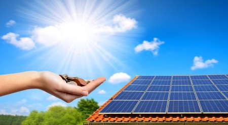 Sonnenkollektor auf dem Dach des Hauses und der Münzen in der Hand. Das Konzept der Geldeinsparung und der sauberen Energie. Standard-Bild