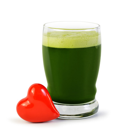 Green barley juice drink in glass and red heart isolated on white background. Detox superfood. The concept of healthy eating.