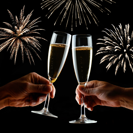 New Years fireworks with clinking glasses of champagne in hands. Holiday background.