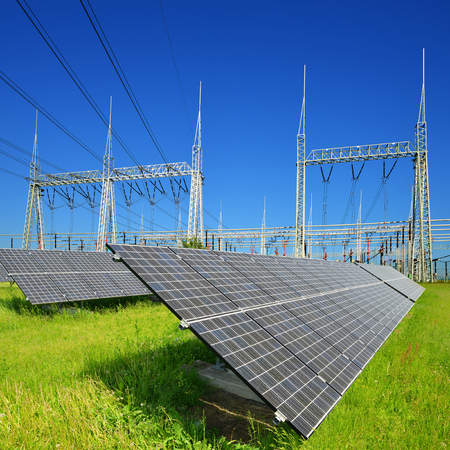 Solar energy panels in the background high voltage power substation. Sustainable resources concept. Stock Photo