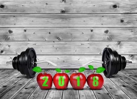 Red apples and large dumbbell on wooden planks. Healthy resolutions for the New Year 2018.