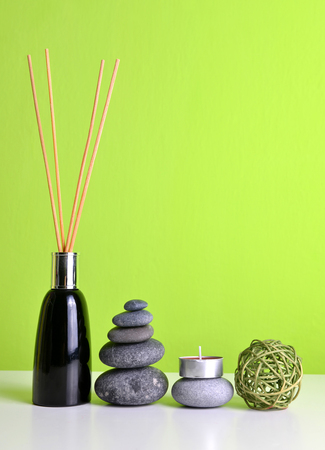 Zen pebbles, candle and air freshener with wooden aroma sticks. Spa and healthcare concept.