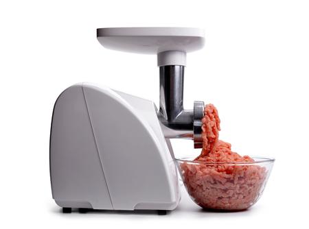 Elektrische Fleischwolf und Schüssel mit Hackfleisch auf einem weißen Hintergrund