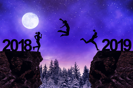Silhouette the girls jump to the New Year 2019 in night.