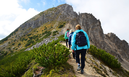 Tourists on a trip in Dolomites mountain , Val di Fiemme, South Tyrol, Italy.